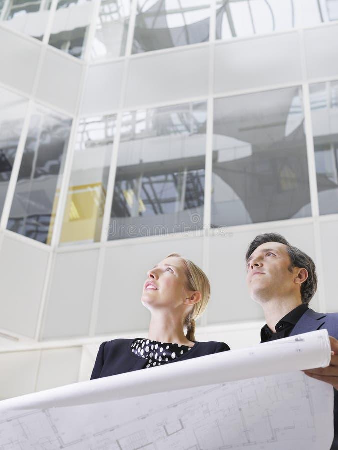 Dos hombres de negocios con el modelo en oficina imagenes de archivo