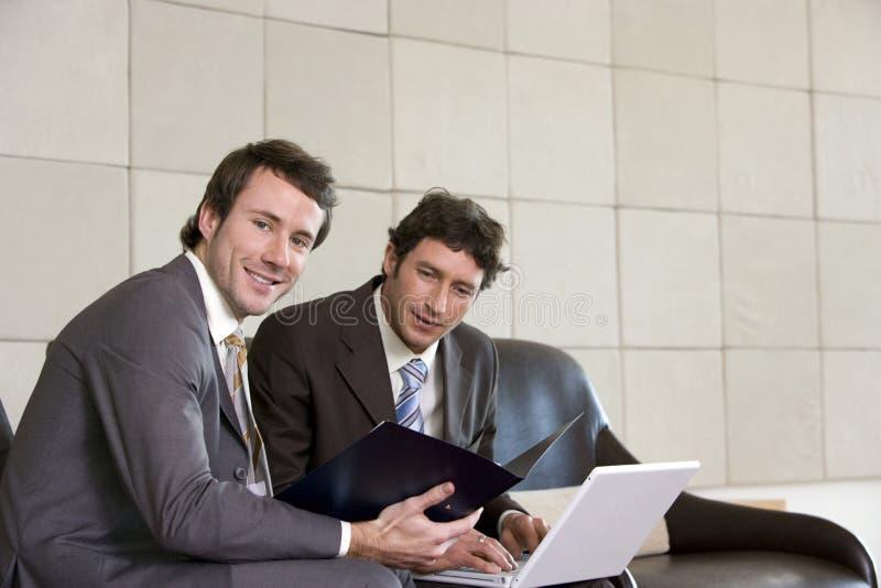 Dos hombres de negocios con la computadora portátil imagenes de archivo