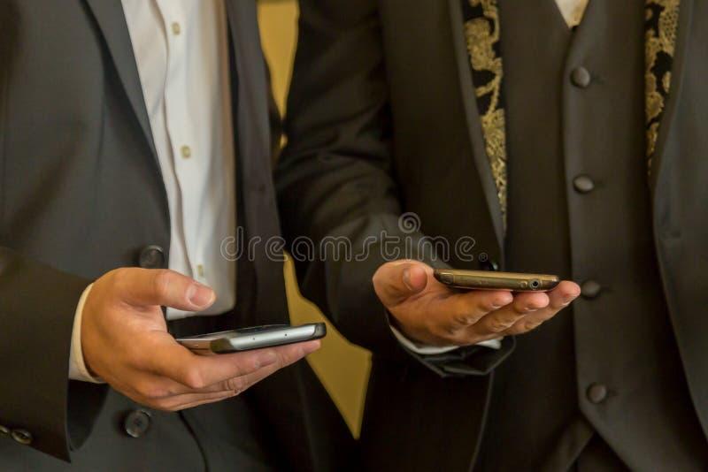 Dos hombres de negocios con los teléfonos móviles Gente con los teléfonos móviles contemporáneos imagen de archivo