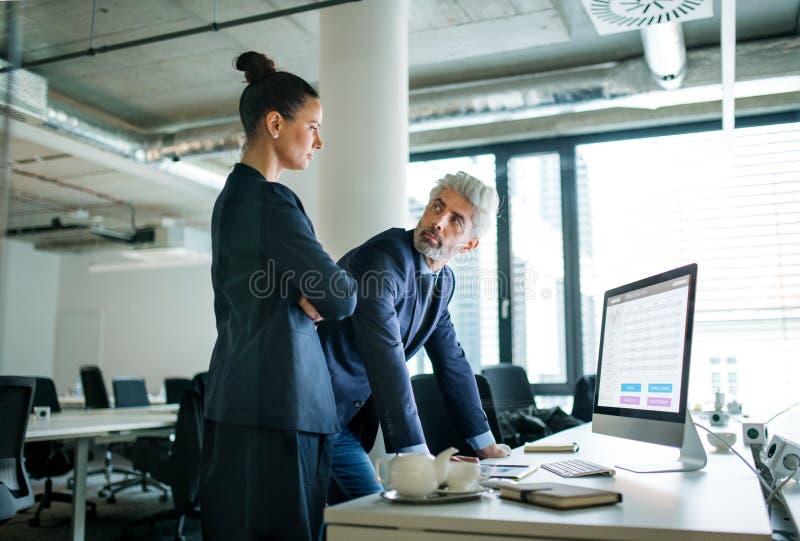 Dos hombres de negocios con un ordenador en una oficina, trabajando imagen de archivo