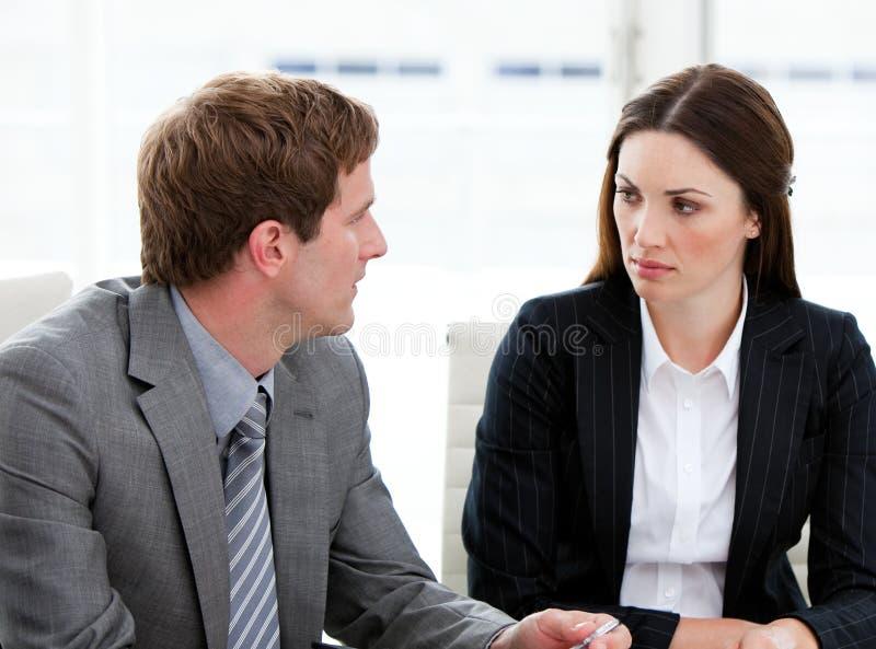 Dos hombres de negocios concentrados que hablan junto fotografía de archivo