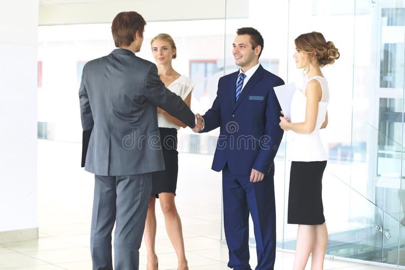 Dos hombres de negocios confiados que sacuden las manos y que sonríen mientras que se coloca en la oficina así como el grupo de c imágenes de archivo libres de regalías