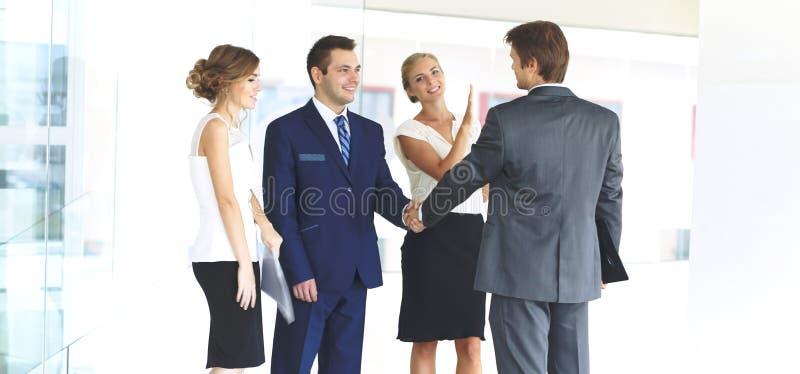 Dos hombres de negocios confiados que sacuden las manos y que sonríen mientras que se coloca en la oficina así como el grupo de c foto de archivo