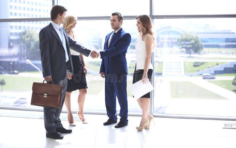 Dos hombres de negocios confiados que sacuden las manos y que sonríen mientras que se coloca en la oficina así como el grupo de c foto de archivo libre de regalías