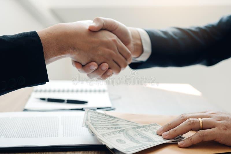 Dos hombres de negocios corporativos que sacuden las manos mientras que un dinero de los lugares del hombre en el documento en si imagenes de archivo