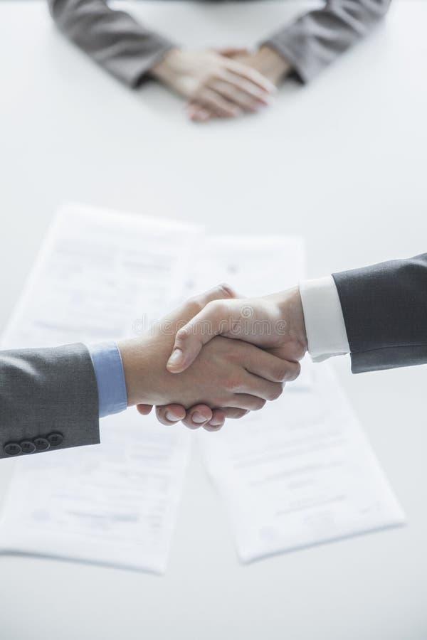 Dos hombres de negocios de la sacudida entregan la tabla, manos solamente imagenes de archivo