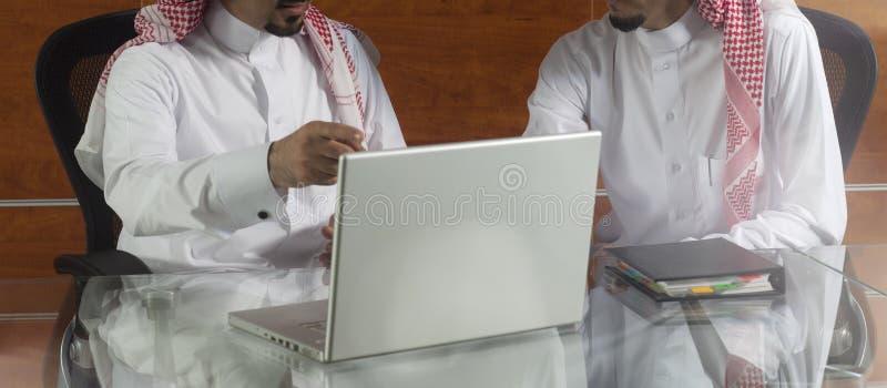 Dos hombres de negocios del saudí que trabajan en un ordenador portátil foto de archivo