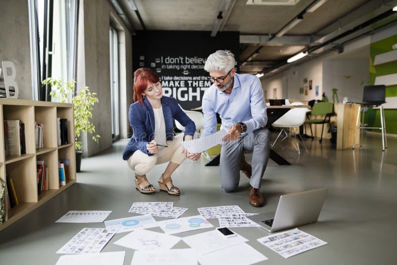 Dos hombres de negocios en la oficina que consultan un proyecto junto imagenes de archivo