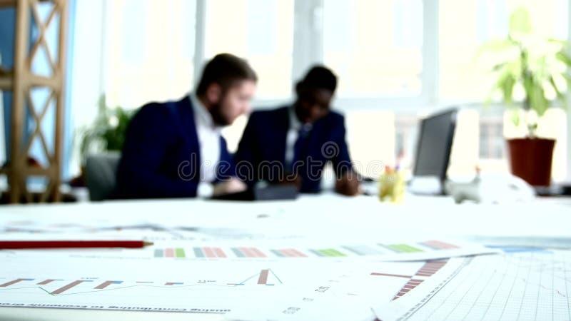 Dos hombres de negocios en trajes azules son estimaciones foco metrajes