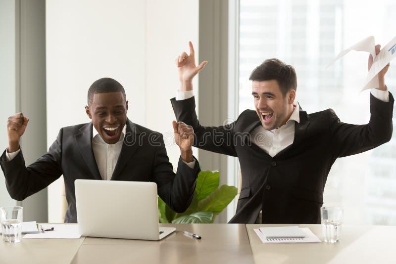 Dos hombres de negocios felices que aumentan las manos acercan al ordenador portátil, celebrando el suc fotografía de archivo