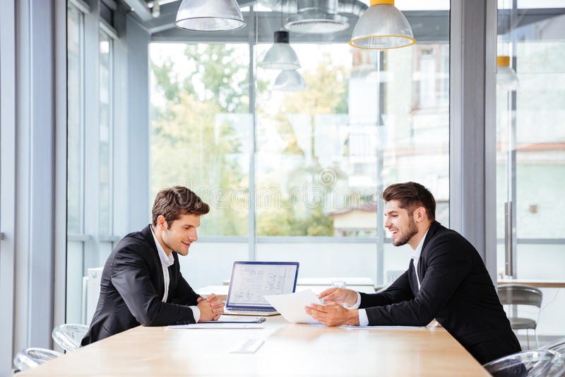 Dos hombres de negocios felices que trabajan junto usando el ordenador portátil en la reunión de negocios imágenes de archivo libres de regalías