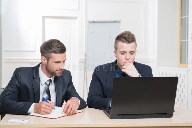 Dos hombres de negocios hermosos en la oficina que trabaja en alguno imagen de archivo