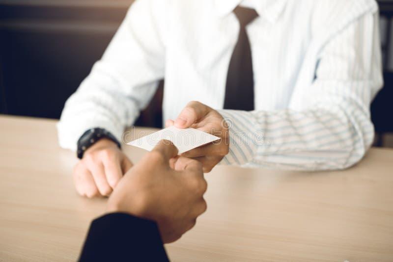 Dos hombres de negocios intercambiaron las tarjetas de visita blancas en una tabla de madera fotografía de archivo
