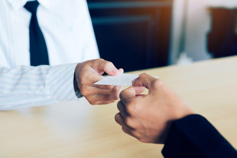 Dos hombres de negocios intercambiaron las tarjetas de visita blancas en una tabla de madera imagen de archivo