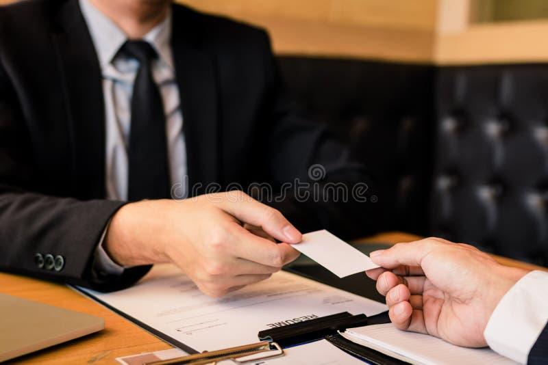 Dos hombres de negocios intercambiaron las tarjetas de visita blancas en una tabla de madera en oficina imagen de archivo