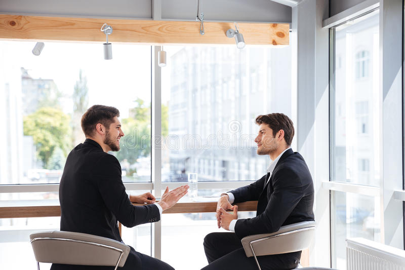 Dos hombres de negocios jovenes hermosos que hablan en oficina imágenes de archivo libres de regalías