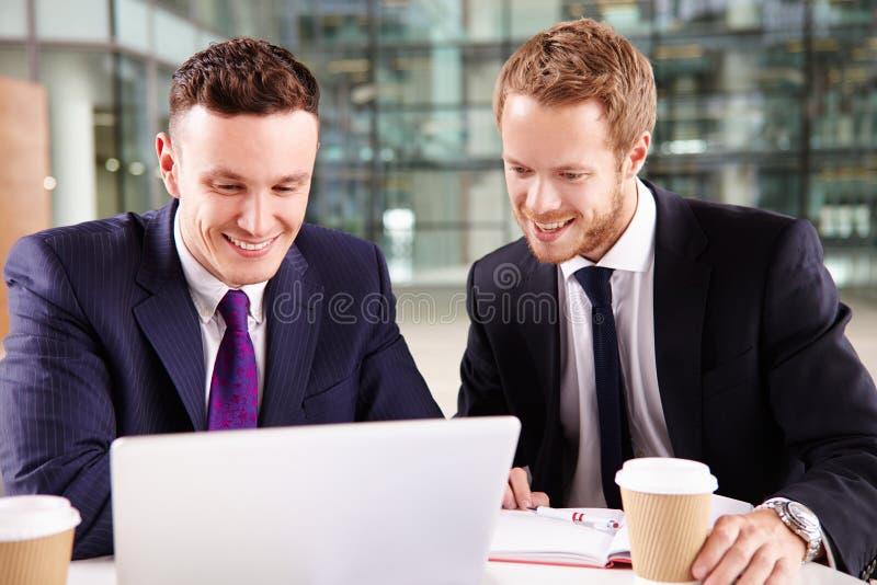 Dos hombres de negocios jovenes que comen café, usando un ordenador portátil fotografía de archivo libre de regalías