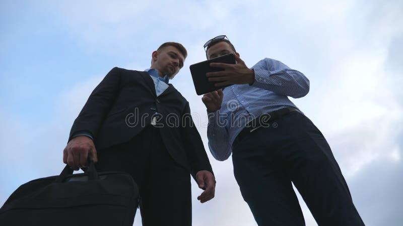 Dos hombres de negocios jovenes que hablan y que usan la PC de la tableta al aire libre Hombres de negocios que trabajan en la ta imagenes de archivo