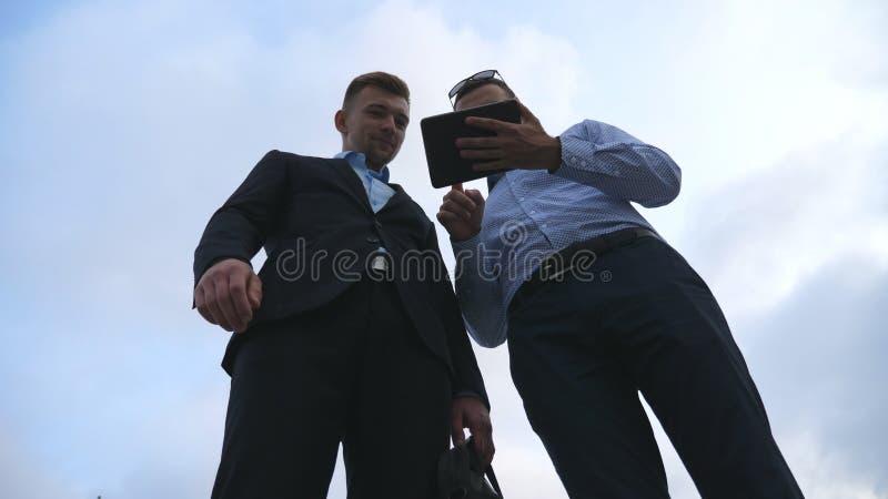 Dos hombres de negocios jovenes que hablan y que usan la PC de la tableta al aire libre Hombres de negocios que trabajan en la ta imagen de archivo