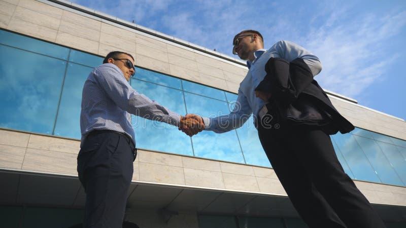 Dos hombres de negocios jovenes que se encuentran cerca de oficina y que se saludan Hombre de negocios que pasa una cartera negra fotos de archivo