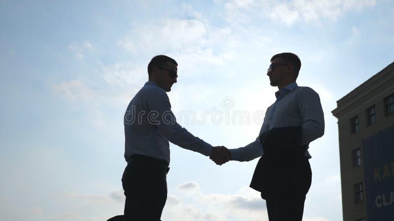 Dos hombres de negocios jovenes que se encuentran en la ciudad y que se saludan Los colegas sacuden las manos al aire libre Mano  imágenes de archivo libres de regalías