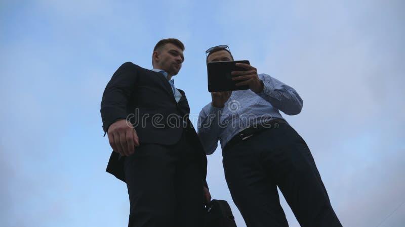 Dos hombres de negocios jovenes resuelven, sacuden las manos y hablar al aire libre Hombres de negocios que usan la PC de la tabl fotos de archivo libres de regalías