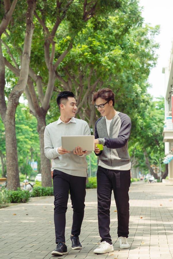 Dos hombres de negocios jovenes sonrientes que caminan y que hablan en la ciudad imagenes de archivo