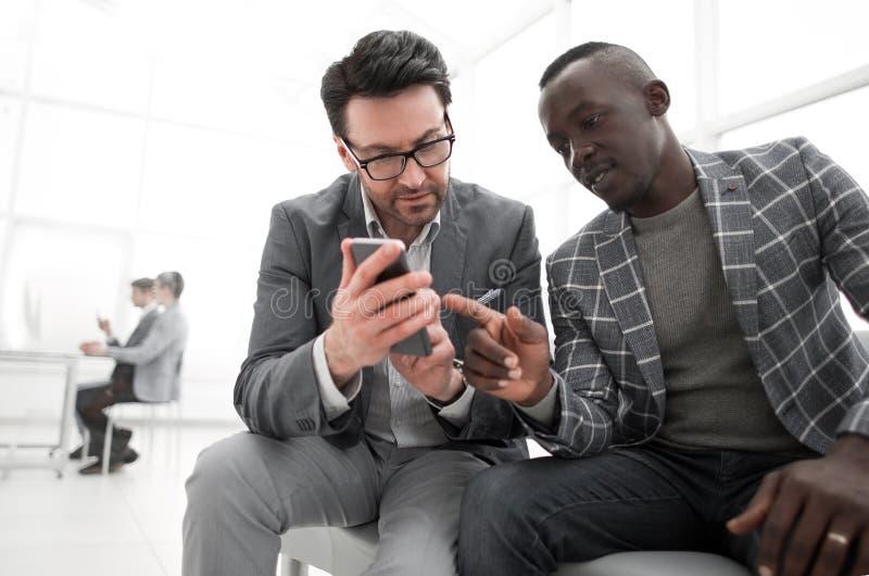 Dos hombres de negocios de los socios que miran el medios contenido en un smartphone imagenes de archivo