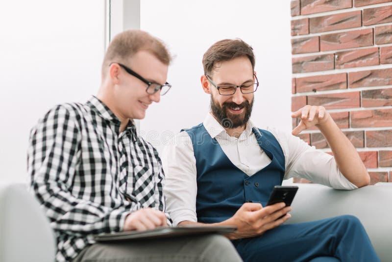 Dos hombres de negocios de los socios que miran el medios contenido en un smartphone fotos de archivo