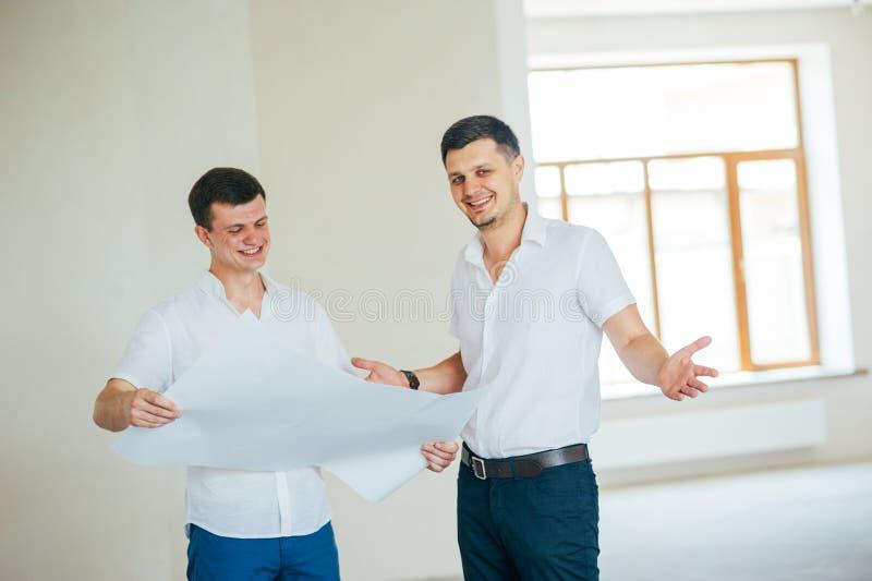 Dos hombres de negocios o engeners que trabajan y que discuten el dibujo plano de la casa durante la construcci?n y el proceso de fotos de archivo