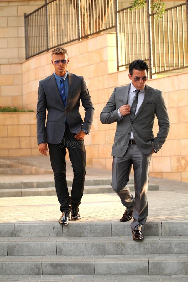 Dos hombres de negocios que caminan abajo de las escaleras cercanas, Sunglass imagen de archivo