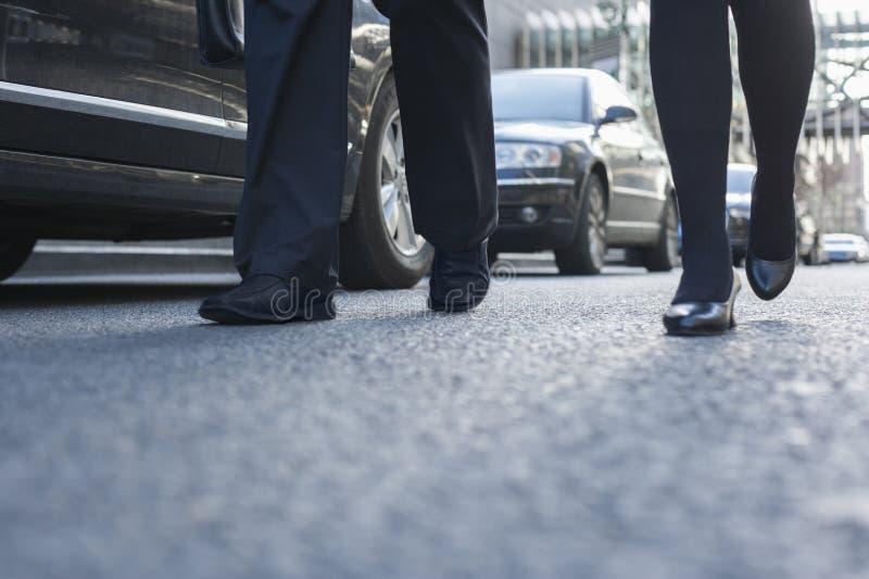 Dos hombres de negocios que caminan abajo de una calle de la ciudad, piernas solamente fotos de archivo libres de regalías