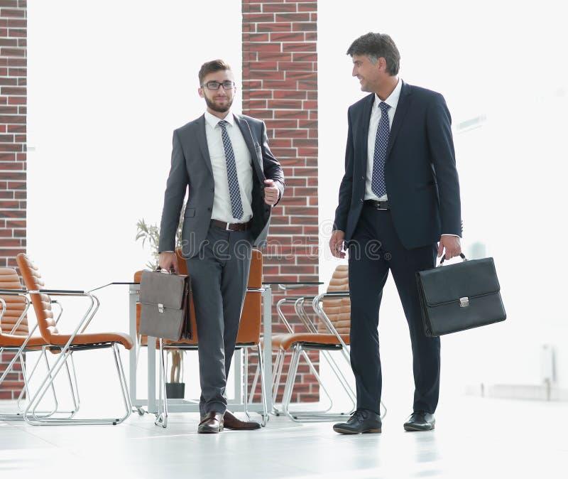 Dos hombres de negocios que caminan adelante en el edificio de oficinas moderno imagen de archivo libre de regalías