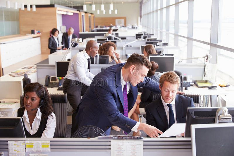Dos hombres de negocios que discuten el trabajo en una oficina ocupada, abierta del plan imágenes de archivo libres de regalías