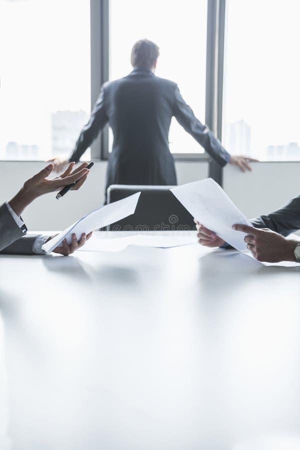 Dos hombres de negocios que discuten y que gesticulan sobre la tabla mientras que otro mira hacia fuera la ventana, manos solament imagen de archivo