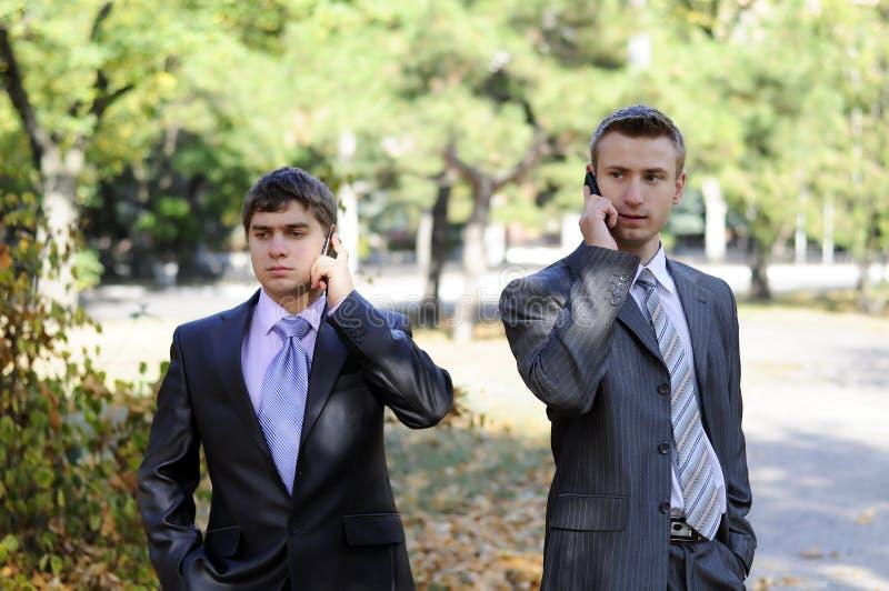 Dos hombres de negocios que hablan en el teléfono imagen de archivo libre de regalías