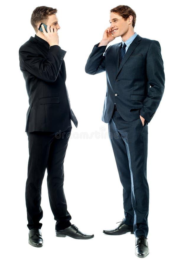 Dos hombres de negocios que hablan en el teléfono móvil fotos de archivo