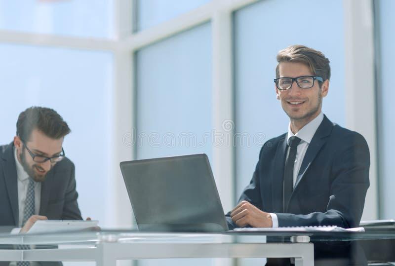 Dos hombres de negocios que hablan sentarse en un escritorio imagen de archivo