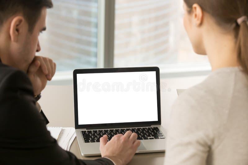 Dos hombres de negocios que miran mofa encima de la pantalla en blanco del ordenador portátil imagen de archivo