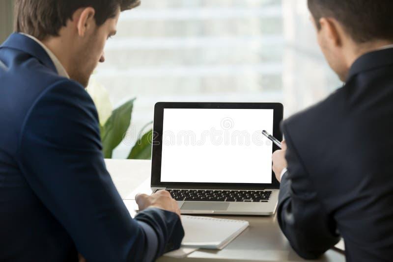 Dos hombres de negocios que miran mofa encima de la pantalla en blanco del ordenador portátil imagen de archivo libre de regalías
