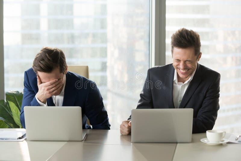 Dos hombres de negocios que ríen hacia fuera emociones positivas ruidosas, buenas del wor imagenes de archivo