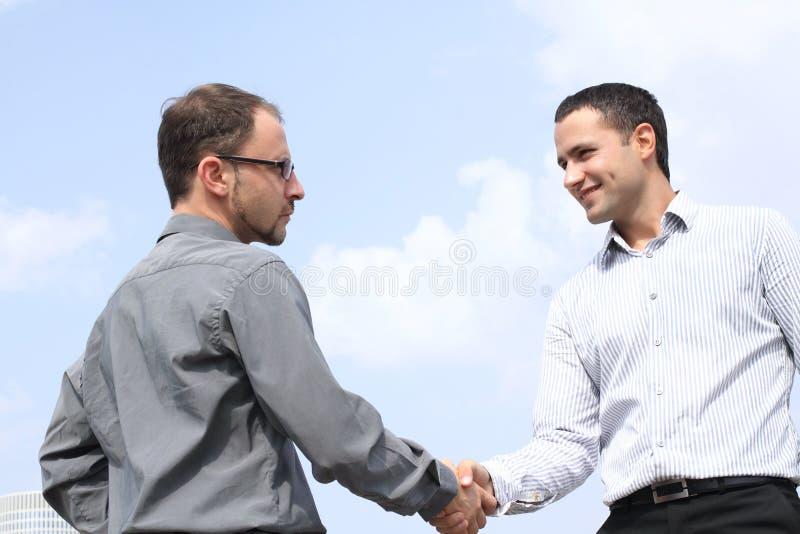 Dos hombres de negocios que sacuden las manos en fondo del cielo fotos de archivo