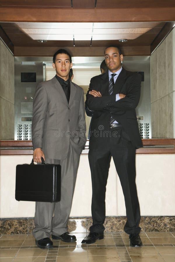 Dos hombres de negocios que se colocan en pasillo fotografía de archivo