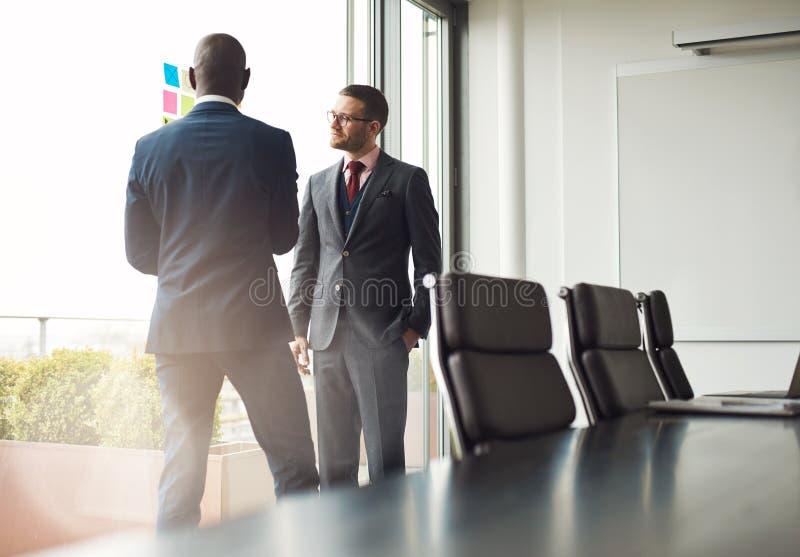Dos hombres de negocios que se colocan que hablan junto imagen de archivo