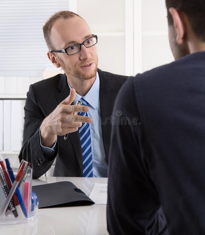 Dos hombres de negocios que se sientan en la oficina: reunión o entrevista de trabajo fotos de archivo