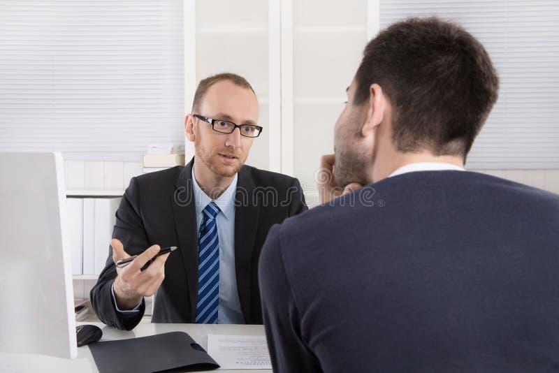 Dos hombres de negocios que se sientan en la oficina: reunión o entrevista de trabajo imagenes de archivo