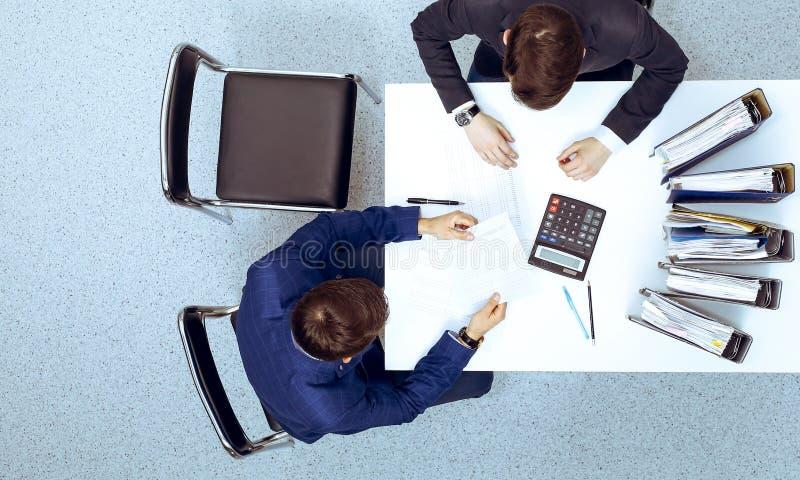 Dos hombres de negocios que se sientan en la tabla, visi?n desde arriba Contable o inspector financiero que hace el informe, calc fotografía de archivo libre de regalías