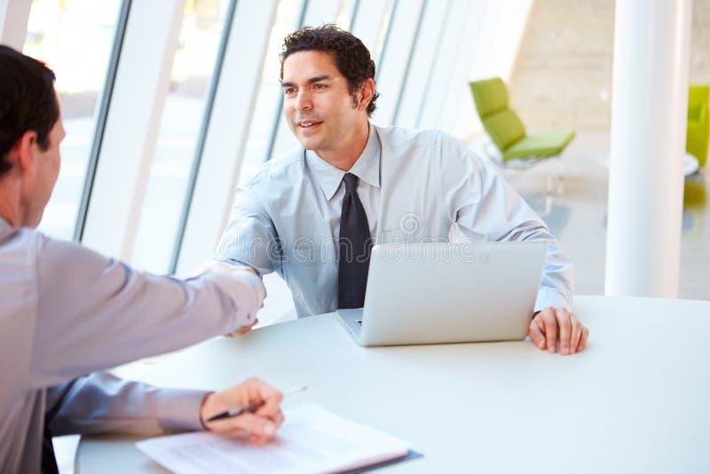 Dos hombres de negocios que tienen reunión alrededor del vector en oficina moderna imagenes de archivo