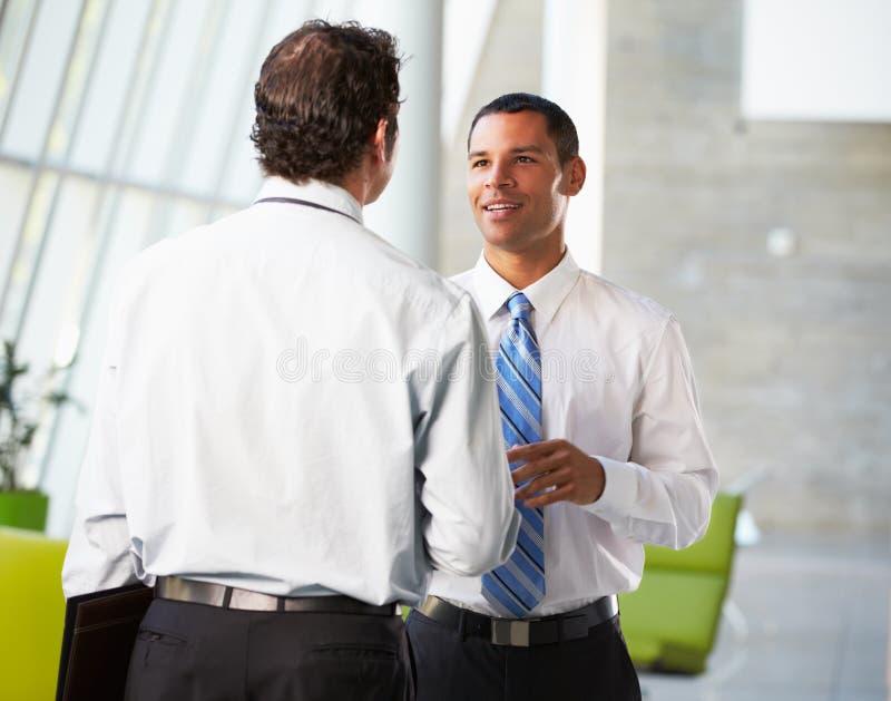 Dos hombres de negocios que tienen reunión informal en oficina moderna foto de archivo