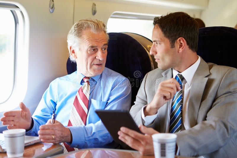 Dos hombres de negocios que tienen reunión sobre el tren foto de archivo libre de regalías